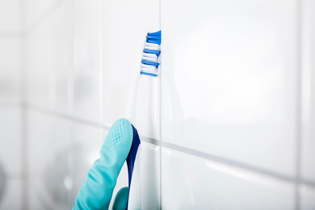 Close-up Of Person Hand Cleaning The Dirty White Tile Of The Wall Using Brush