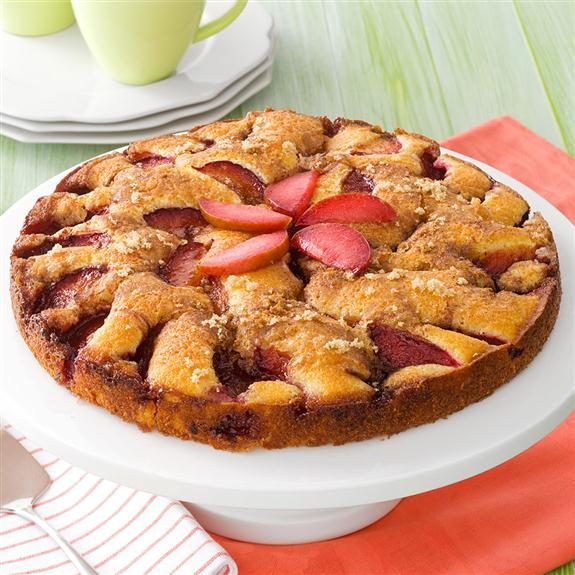 Fresh plum kuchen topped with sliced strawberries in a star shape resting on a cake stand