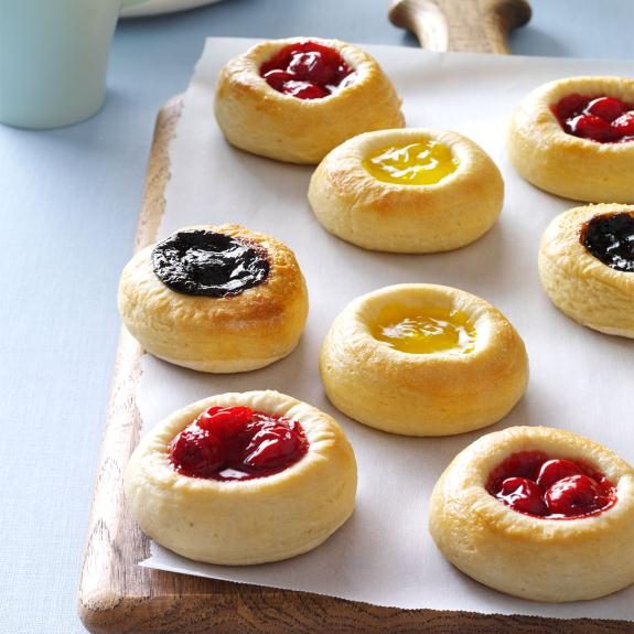 Bohemian kolaches of different flavors lined up on parchment paper