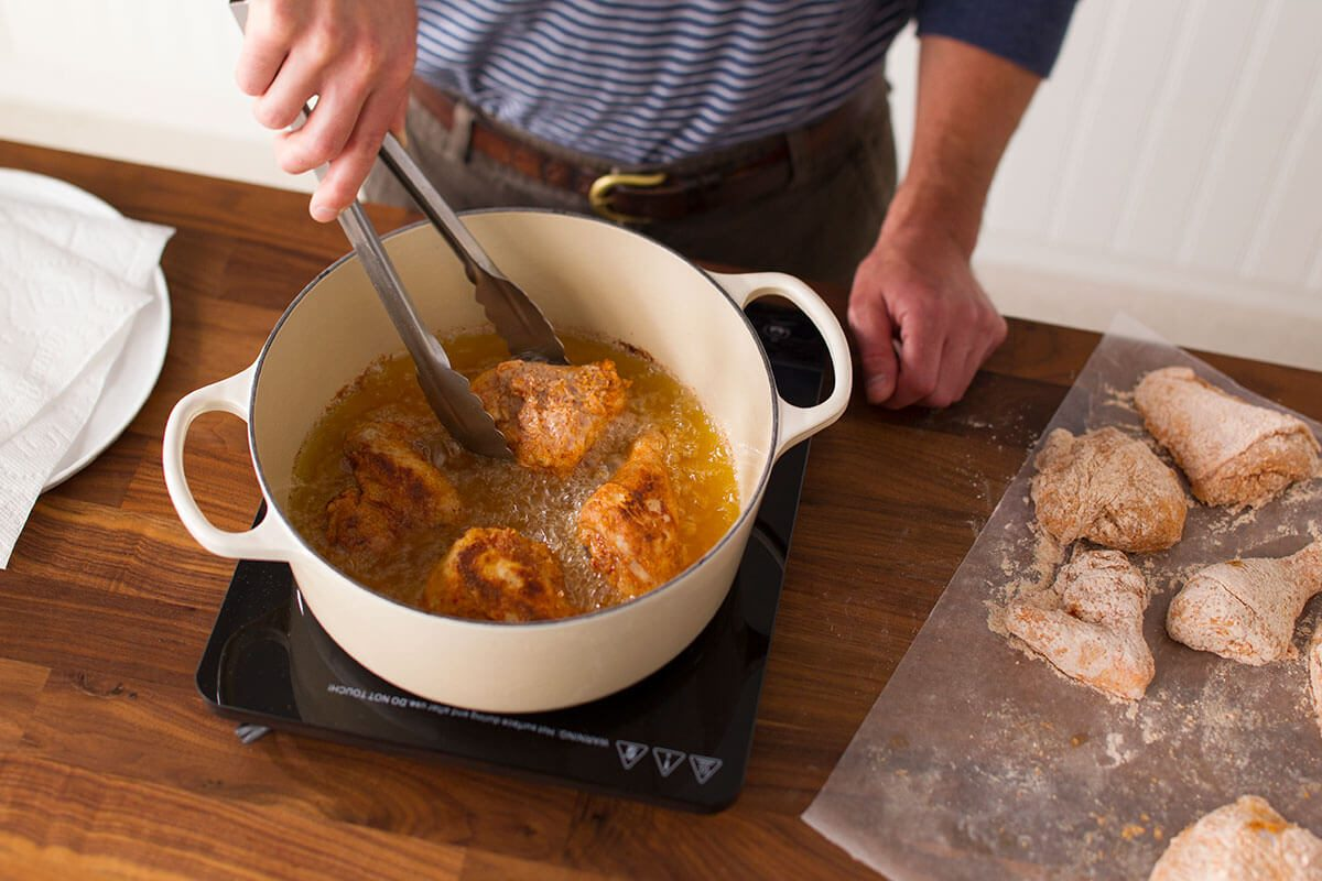 Person lowering chicken into a pot to deep fry on the stove