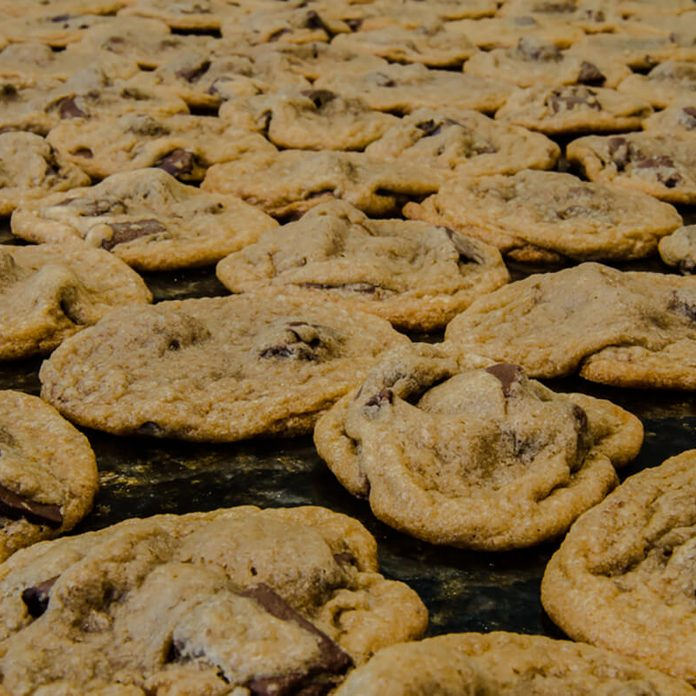 Homemade chocolate chip cookies spread out to cool on a granite countertop