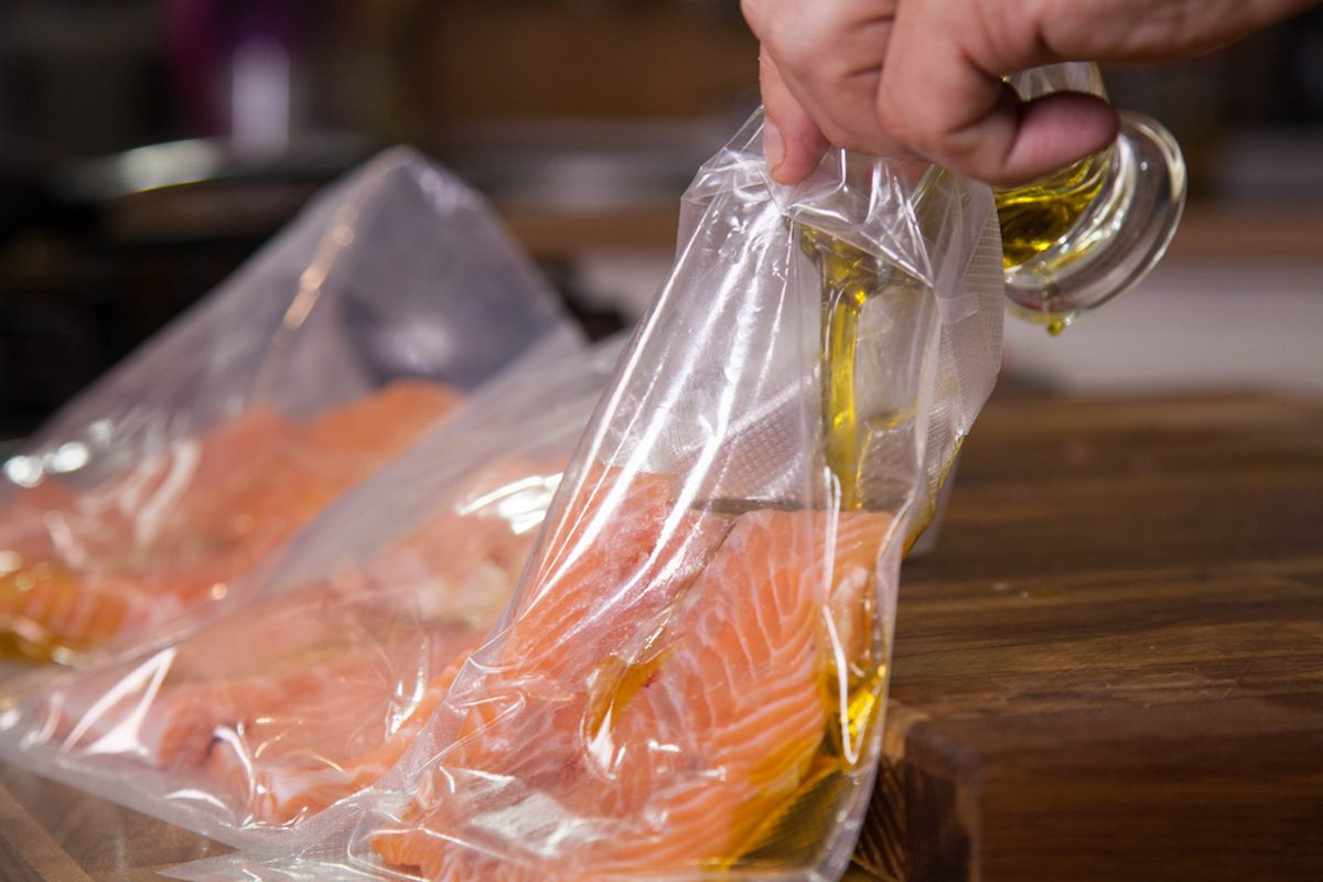 Preparing salmon for sous-vide cooking and pouring olive oil in vacuumed bag.