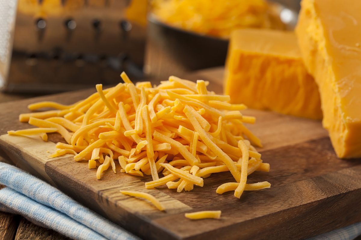 Organic Shredded Sharp Cheddar Cheese on a Cutting Board