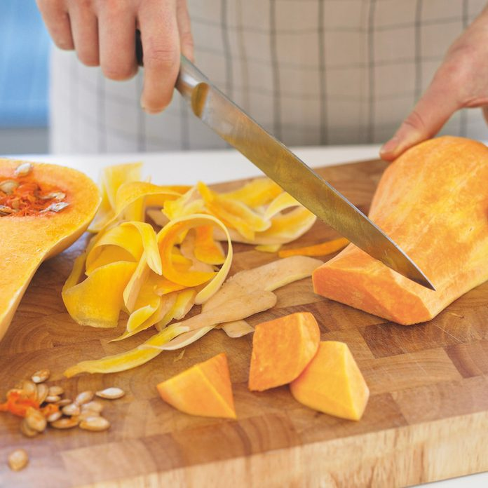 A person cutting a butternut squash on a wooden cuting board.