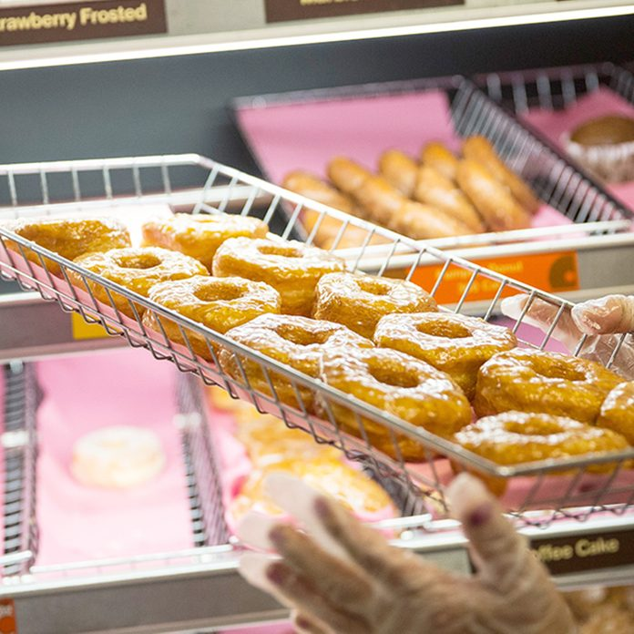 "NEW YORK, NY - NOVEMBER 03: A Dunkin' Donuts employee places a fresh tray of ""croissant doughnuts,"" on the shelf on November 3, 2014 in New York City. The pastry, which began selling at Dunkin' Donuts two days ago, is based on baker Dominque Ansel's hybrid pastry, the ""cronut,"" which came to popularity in the summer of 2013. (Photo by Andrew Burton/Getty Images)"