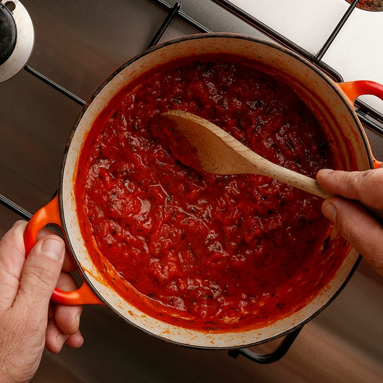 Cooking a traditional gormet tomato sauce and wooden spoon, on a stainless steal hob, shot from above