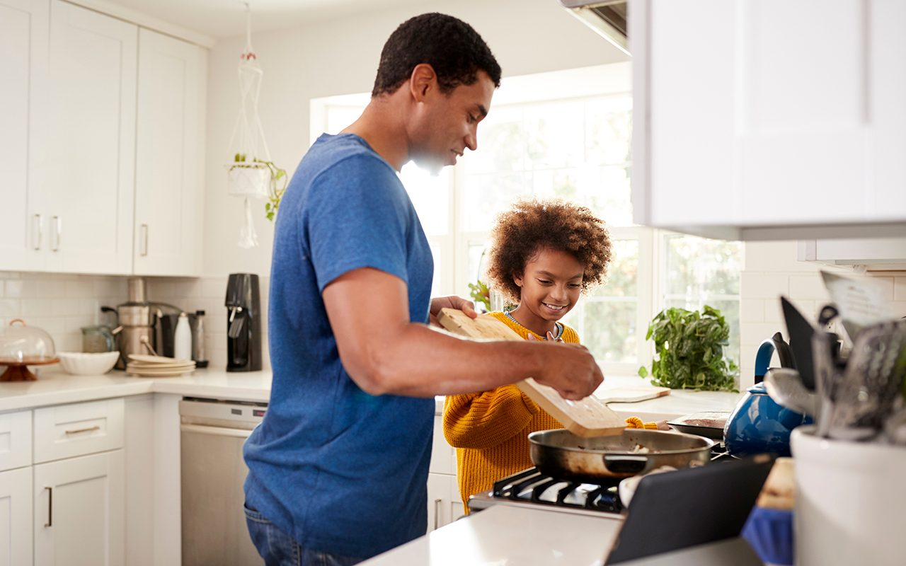 Pre-teen girl and her father standing at hob in the kitchen preparing food in a frying pan, following a recipe on a tablet computer, backlit