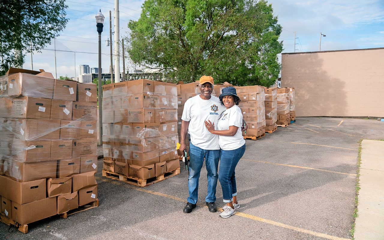 Two people standing side-by-side in front of pallets of food donations