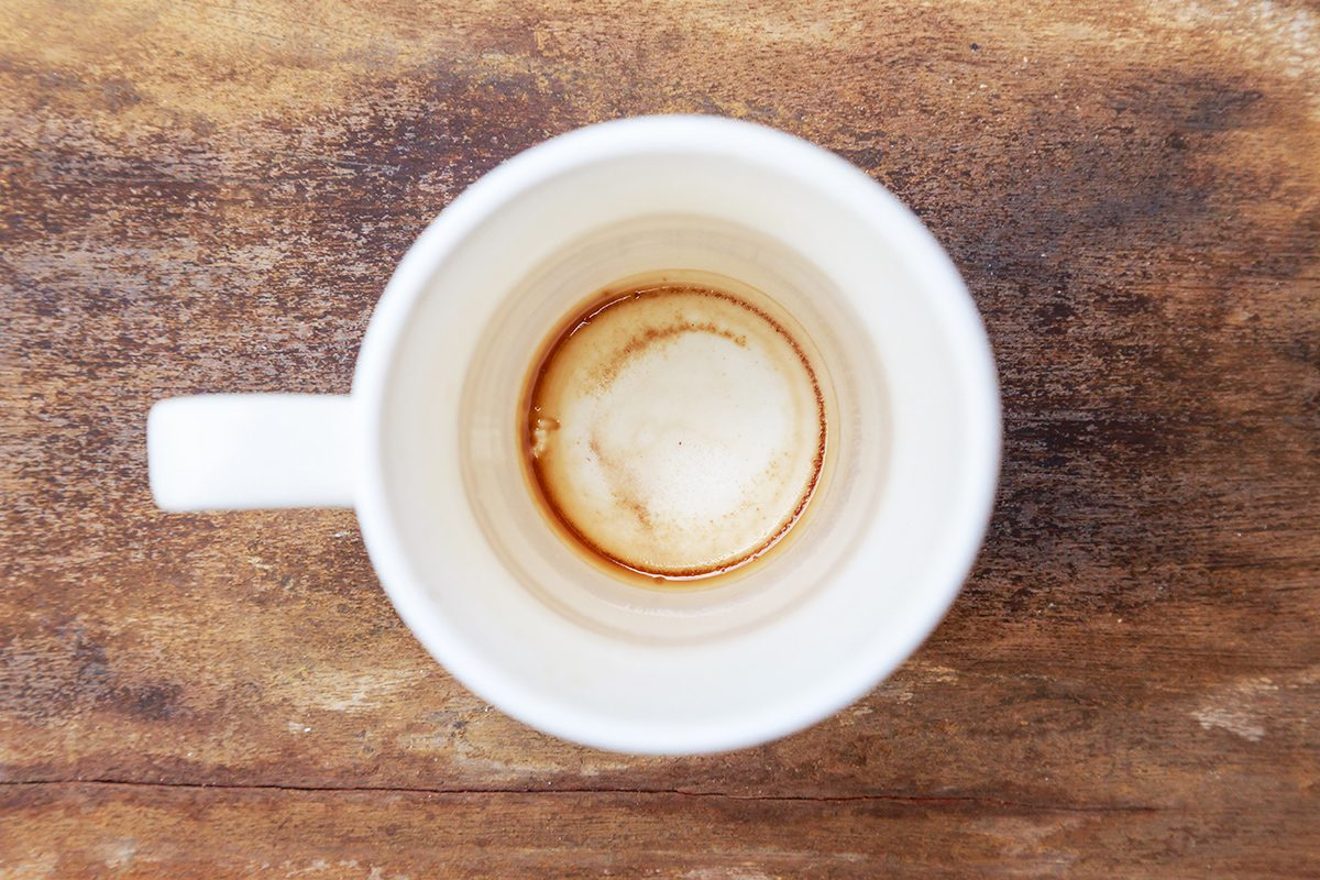 Cup of coffee drying mark in white cup on old wooden background