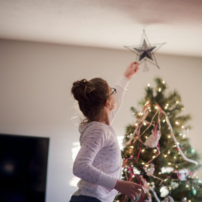 Girl putting up Christmas decorations
