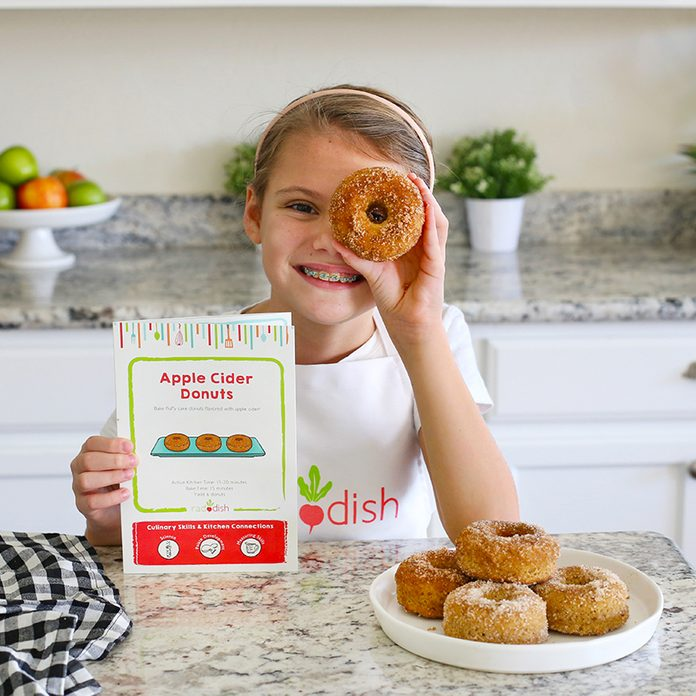 Young kid looking through the hole of a donut and smiling