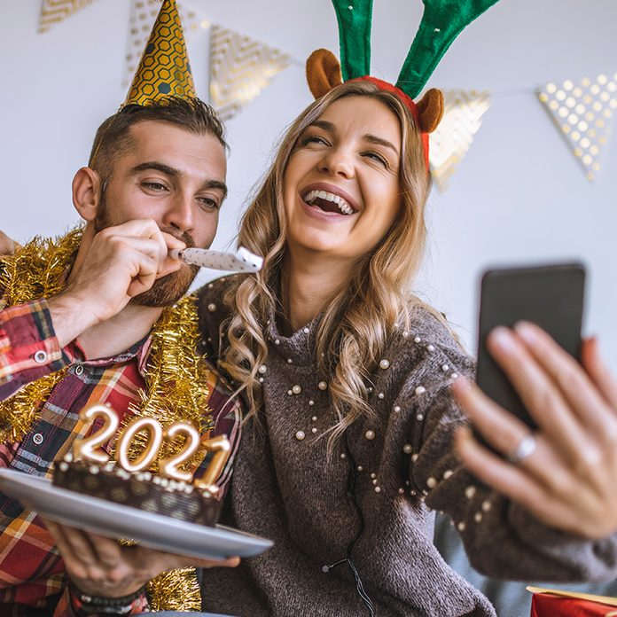 Couple celebrating Christmas at home, holding chocolate cake with lit candles shaped as numbers 2021 and having a video call with friends