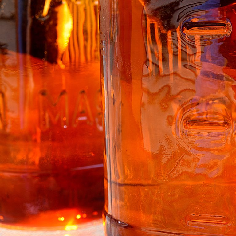 Sun tea being made in mason jars (that's a type of jar its not trademarked) with unintelligible letters on the jars.