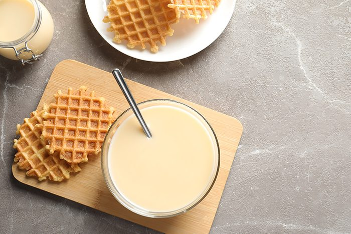 Bowl of condensed milk and waffles served on grey table