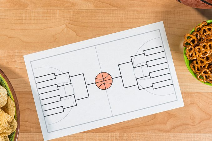 An overhead view of a party for a college basketball tournament with an empty 16 team bracket. There is a bowl of small pretzels, chips and salsa along with a basketball sitting on what looks like a maple wood basketball court. This bracket is for a 16 team single elimination tournament, winner take all, which typically happens in March every year in the US between college basketball teams and many people gamble on the series.