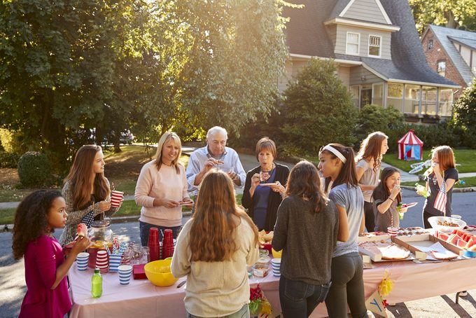 Neighbours talk and eat around a table at a block party;