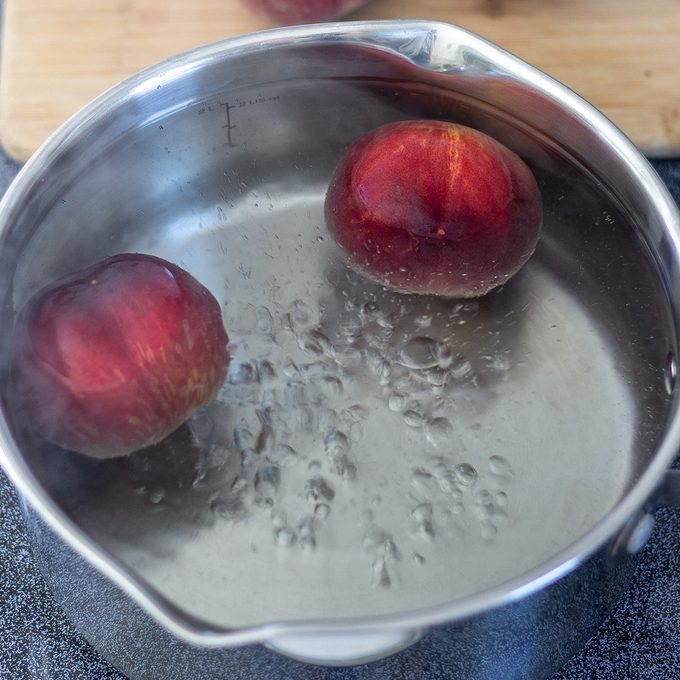 Silver saucepan with whole peaches in boiling water