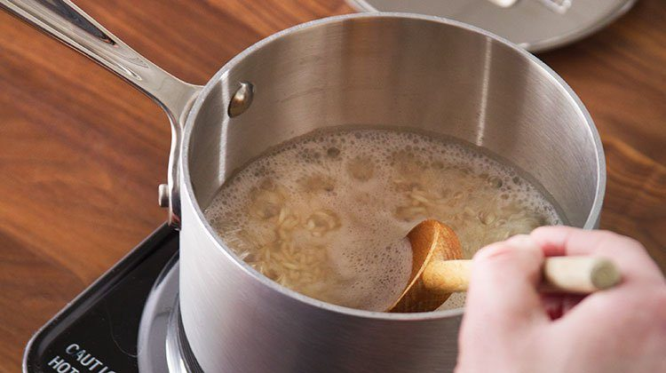 rice simmers on the stove top in a metal pot