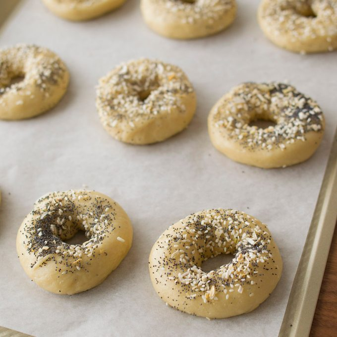 Homemade bagels arranged on a parchment-lined baking sheet.