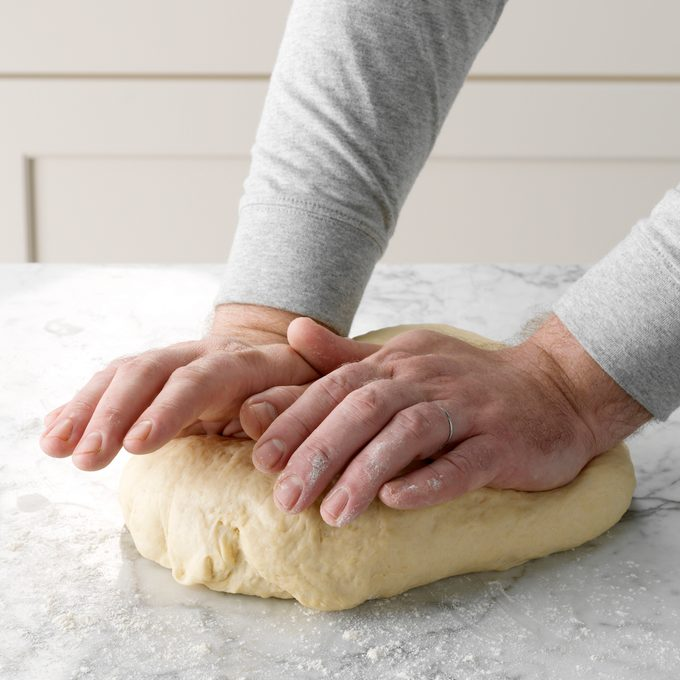 A person kneading dough to make homemade bagels.