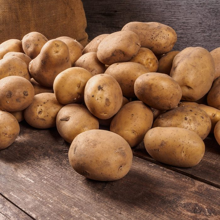Pile of potatoes lying on wooden boards with a potato bag in the background ; Shutterstock ID 347630291