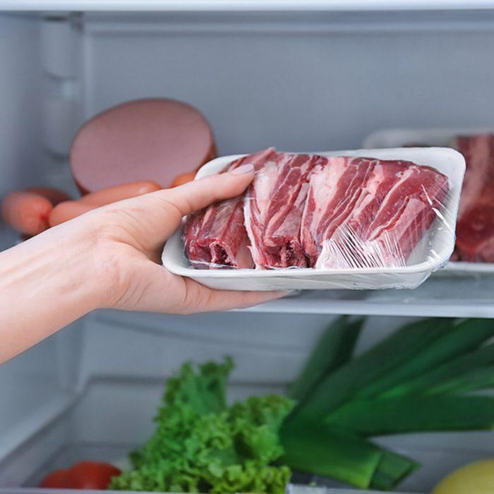 Woman putting raw meat in refrigerator, closeup; Shutterstock ID 795124657