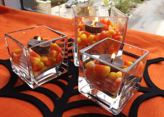 Three candy corn candles making up a centerpiece
