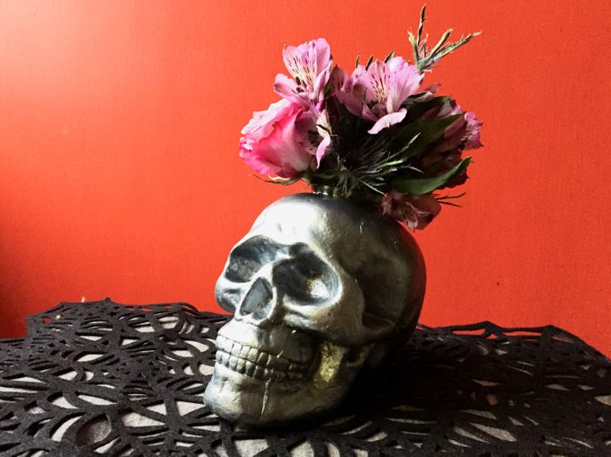 Black skull being used as a vase for pink flowers