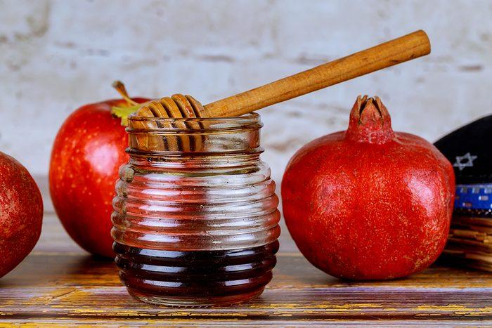 Pouring honey on apple and pomegranate with honey symbols of Jewish New Year Rosh Hashanah.