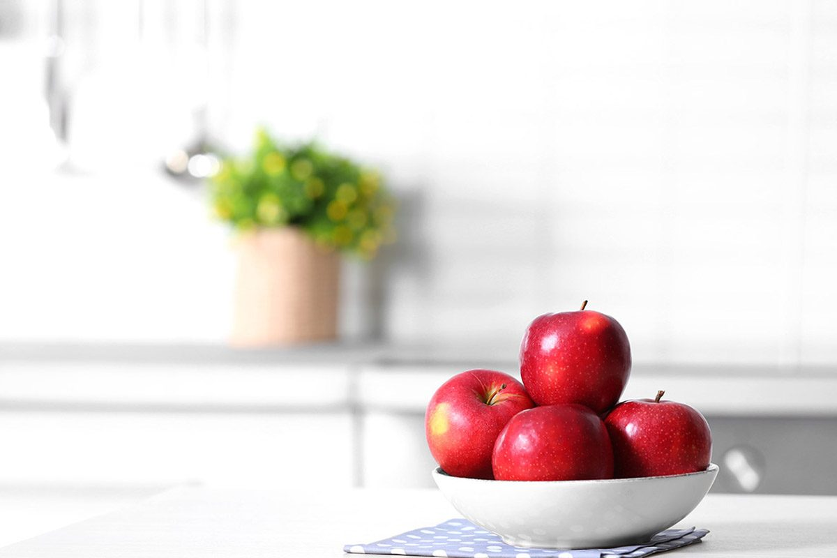 Bowl of fresh red apples on kitchen counter