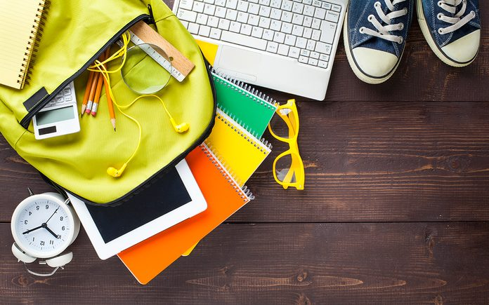 Back to school concept. Backpack with school supplies. Top view. Wooden background. Copy space.