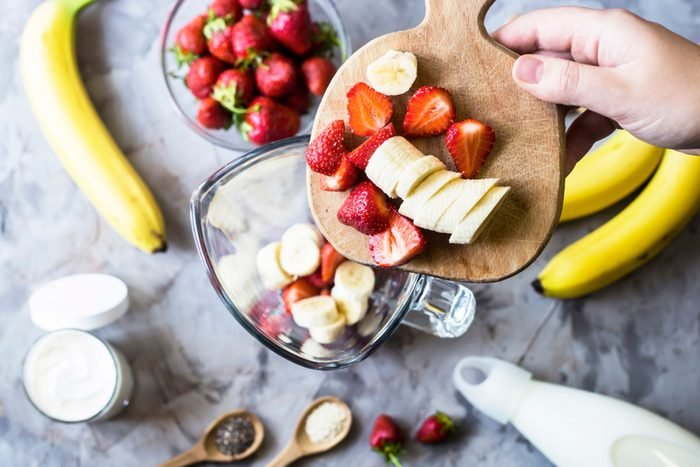Ingredients for making strawberry banana smoothies next to a blender
