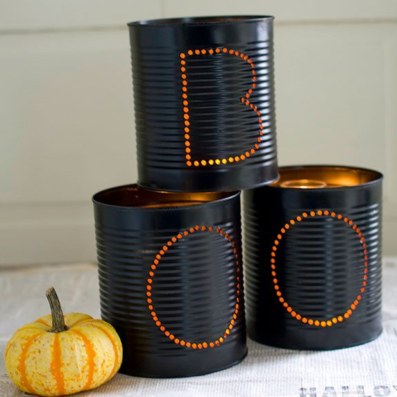 """Black cans stacked together with """"BOO"""" written out in holes on them"""