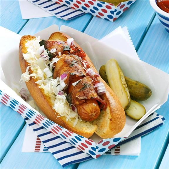 Bacon-wrapped hotdog over-flowing with onions, coleslaw and ketchup beside pickles in a paper dish