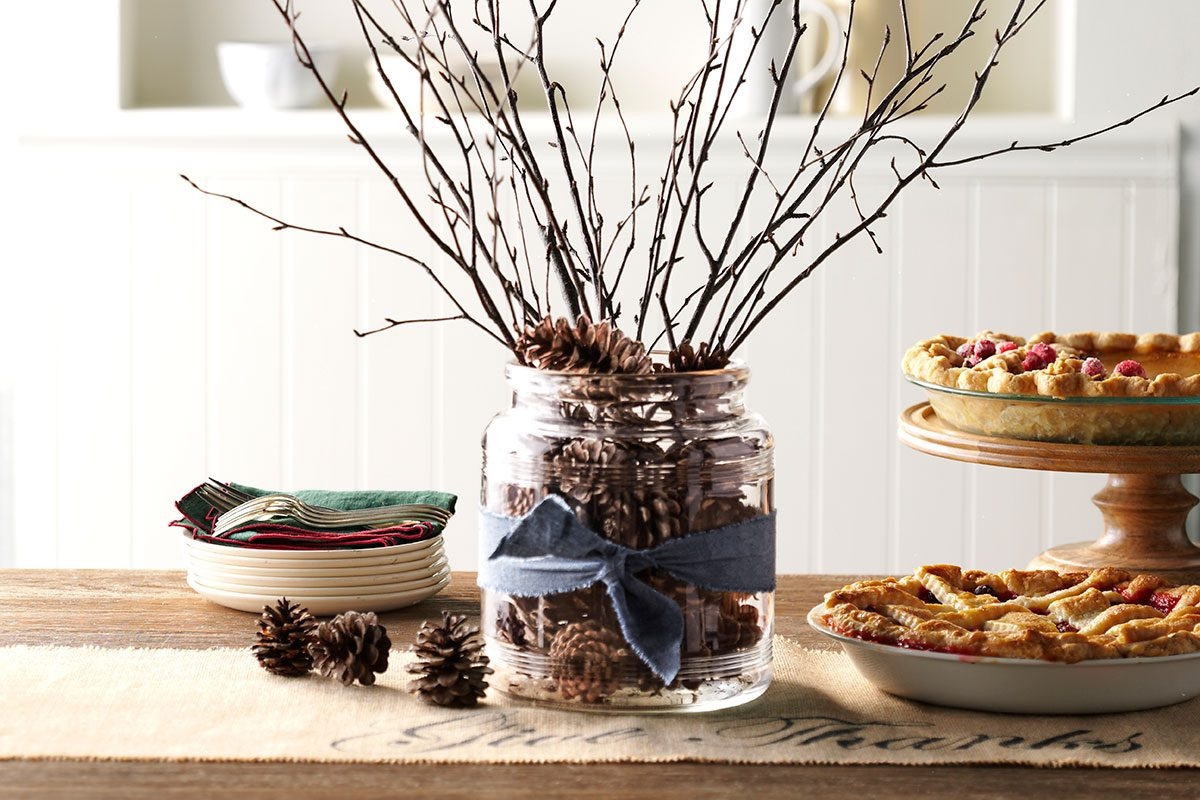 Table with two pies and a branch center piece including a pine cone filled jar