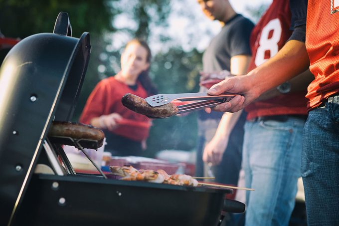 Man Works The Grill At Tailgating Party