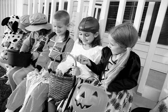 Halloween: Kids Sit On Porch And Look At Halloween Candy