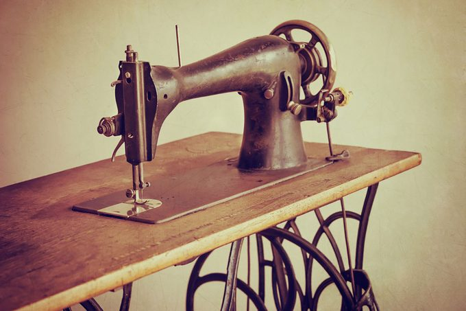 Old sewing machine on textured vintage background