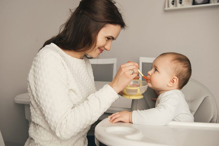 Mother giving food to her baby at home.