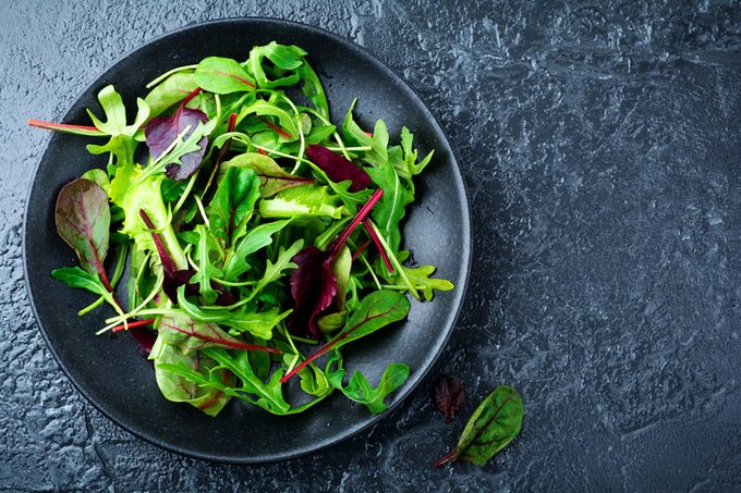 Mix fresh leaves of arugula, lettuce, spinach, beets for salad on a dark stone background.