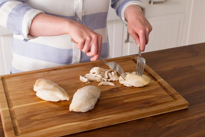 Person using two forks to shred chicken breasts on a wooden cutting board