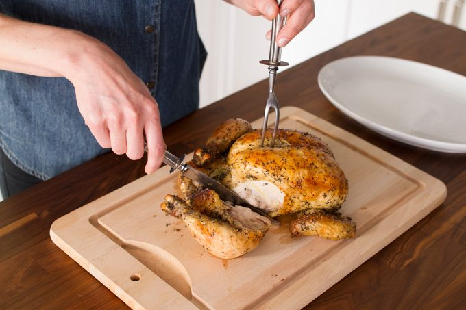 With one hand holding a fork to keep the chicken steady, a leg is sliced cleanly through on a wooden cutting board