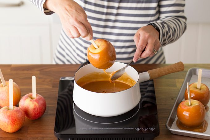Person pulling a homemade caramel apple out of a pot of melted caramel
