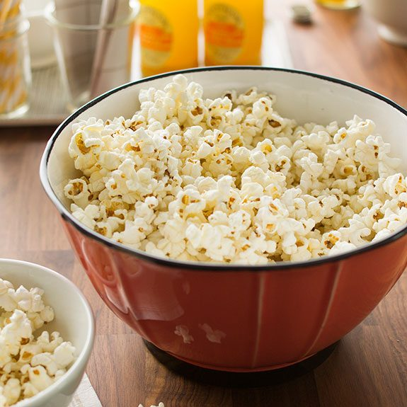 Red bowl filled with popcorn on a wood table