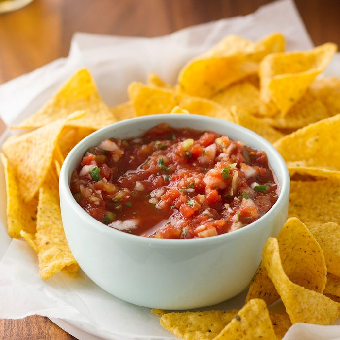 Homemade salsa in a bowl surrounded by tortilla chips