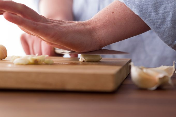 Person using the palm of their hand to press down on a knife to crack a clove of garlic