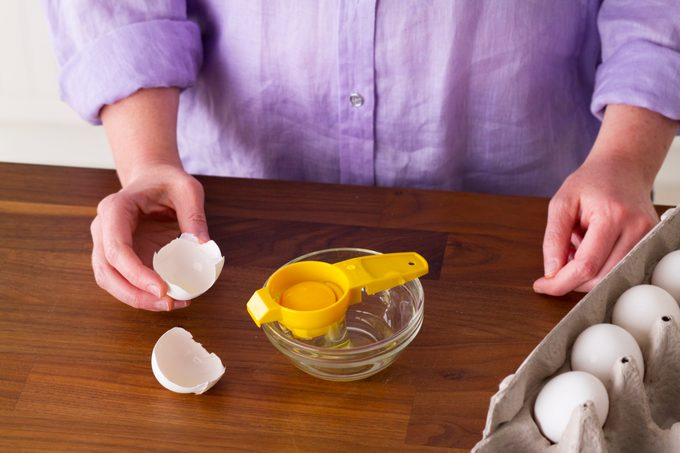 Egg separator over a small glass with a carton of eggs on the side