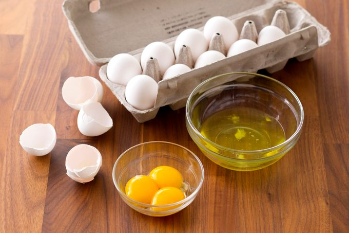 Carton of eggs besides two bowls one with egg whites and the other with yolks