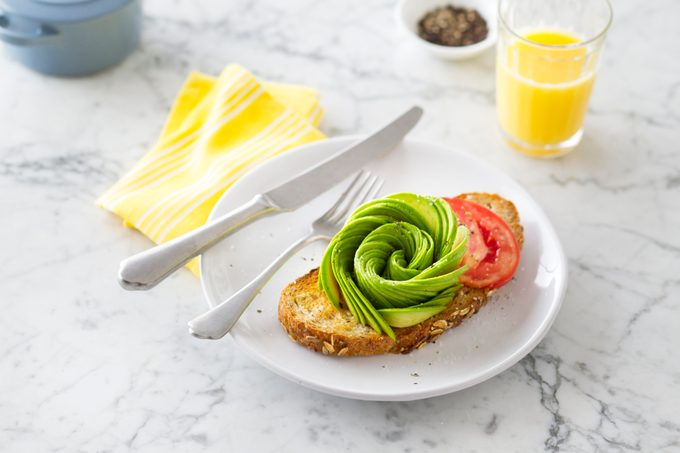 Avocado rose on top of a slice of toast on a plate beside a knife and yellow napkin