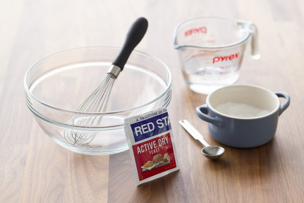 Packet of yeast, measuring cups and a small spoon beside a glass bowl with a whisk in it